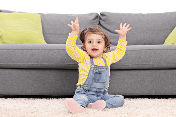 Playful baby girl sitting on the floor next to a modern sofa and
