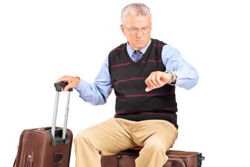 Senior tourist checking the time seated on his luggage