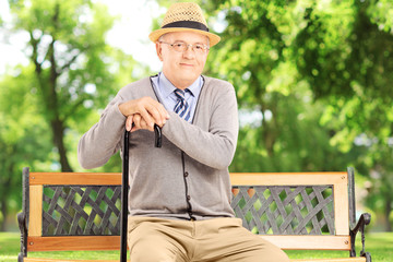 Senior man with cane sitting on a bench and looking at camera