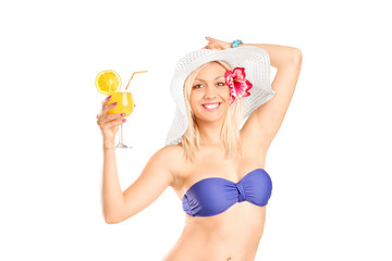 Smiling sexy girl in blue bikini holding a cocktail and looking
