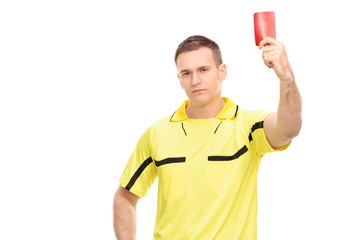 Strict football referee standing and showing a red card