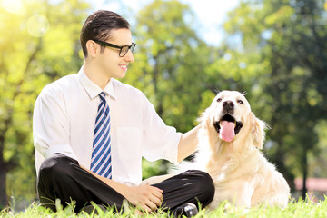 Smiling young businessman with his dog sitting on grass in a par