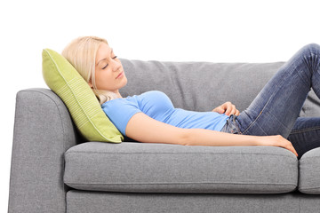 Studio shot of a young blond woman taking a nap on a grey sofa