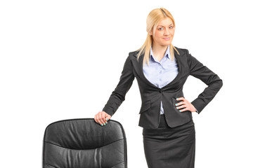 Young blond businesswoman wearing black suit and standing by a c