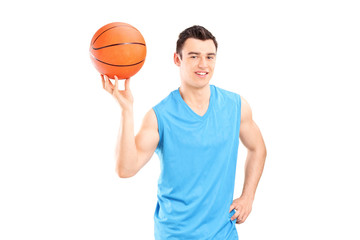 Young smiling basketball player in blue dress posing with a ball