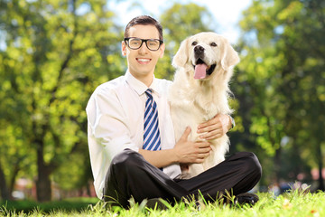 Young smiling man sitting on a green grass and hugging his dog i