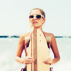 sexy yuong  woman in sunglasses with longboard