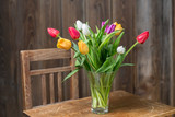 Coloful tulips in a vase on a wooden table - 81033355