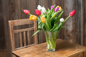 Coloful tulips in a vase on a wooden table