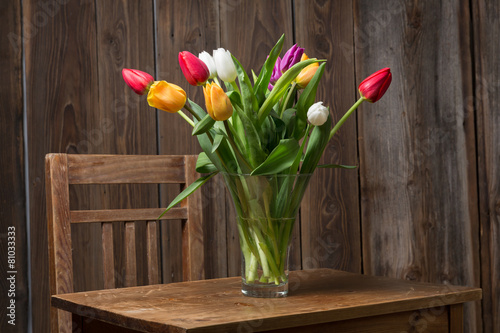 Foto op Canvas Lilac Coloful tulips in a vase on a wooden table