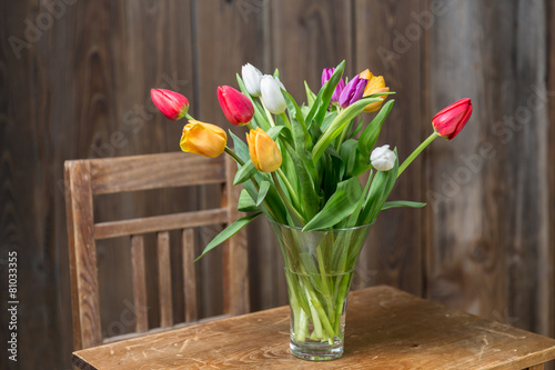 Keuken foto achterwand Lilac Coloful tulips in a vase on a wooden table