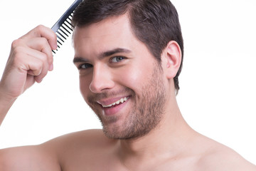 Happy young man combing hair.
