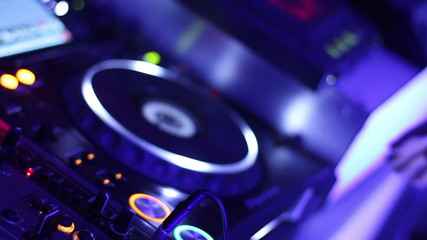 Male DJ hands pressing buttons on control deck, platter turning