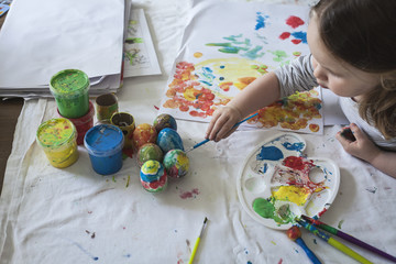 Little girl painting Easter eggs at home