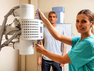 Happy female doctor preparing machine for medical scan