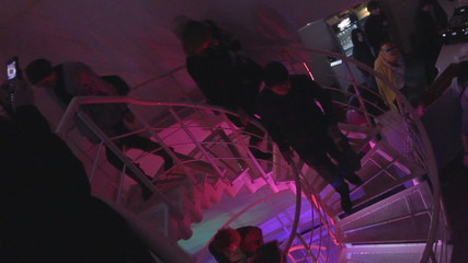 People going up, down stairs, nightclub atmosphere, partying