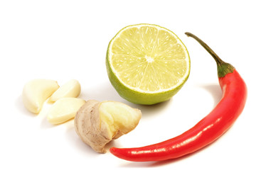 Cloves of garlic, ginger root, half of a lime and a red chili