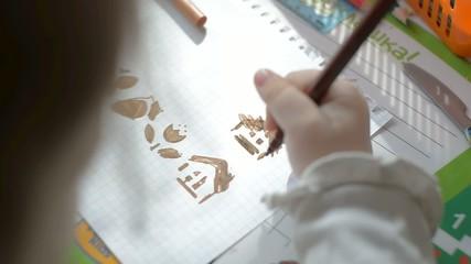 Child draws using a stencil.