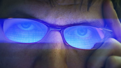 Closeup of glasses wearing men looking into a monitor. 4K UHD