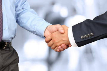 Close-up image of a firm handshake between two colleagues in off
