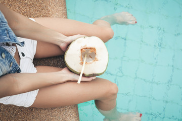 portrait of cute girl with coconut cocktail in the tropical pool