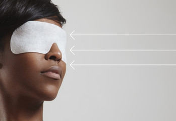 woman with an eye treatment mask and arrows