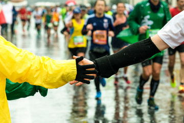 young give his hand to a runner during the marathon