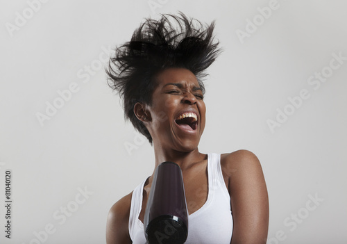 black woman drying hair and singing
