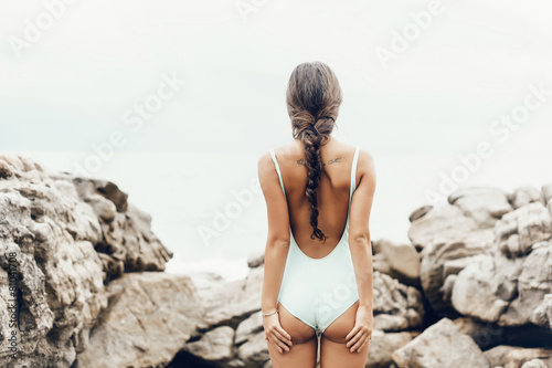 Young woman in a swimsuit standing on the shore