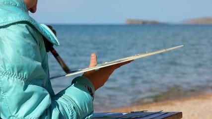 ребёнок рисует на фоне моря