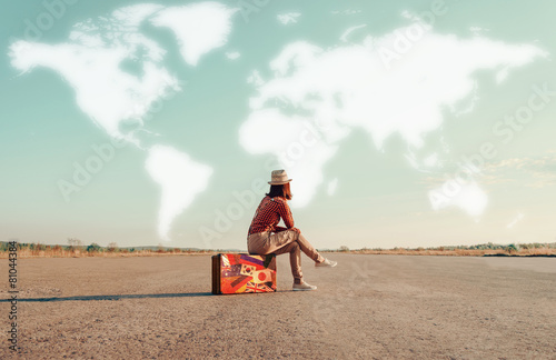 Leinwanddruck Bild Traveler girl sitting on a suitcase