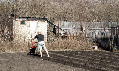 Small rotary cultivator, man  working in garden