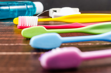 Set of colorful toothbrushs with mountwash and dental floss on b