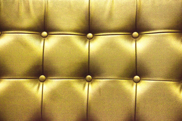 Closeup texture of vintage gold leather sofa for background