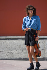 Biracial female violinist posing with instrument