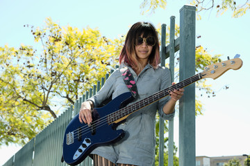 Young lady playing blue bass guitar outside