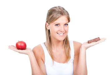 Woman holding apple and candy, fruit or candy dilemma