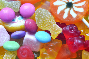 Lollipop, gummy bears and sour candy on colored smarties