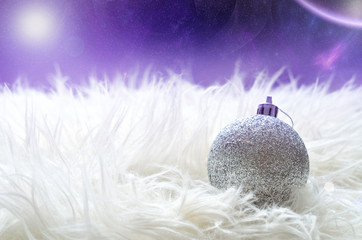 Silver christmas ball lying on a white furry nest