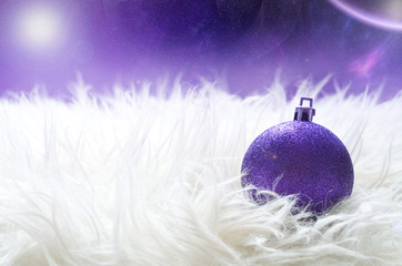 Purple christmas ball lying on a white furry nest