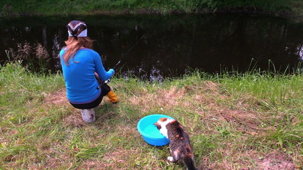 cat with claw catch fish from bowl, woman fishing at pond