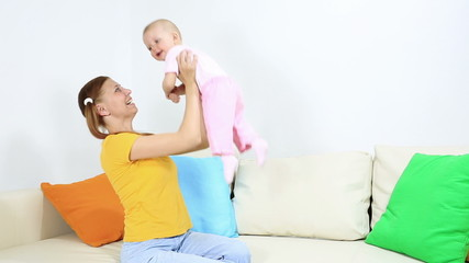 mother and baby in home joy on sofa