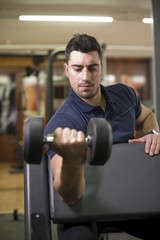 Young man training biceps at gym at curling bench