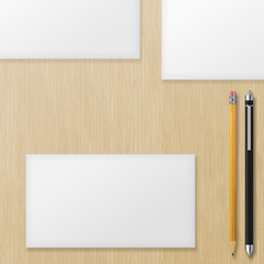 Set of blank envelopes with yellow pencil and pen on wooden back