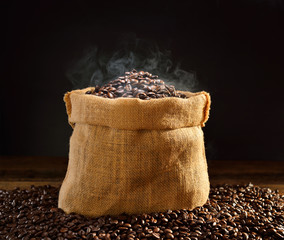 Coffee beans with smoke in burlap sack © amenic181