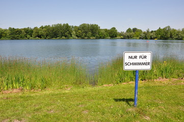 Baggersee mit Hinweisschild