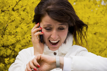 Young woman talking on the phone and looking at wristwatch
