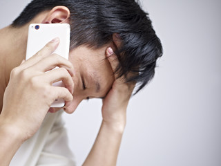 young man talking on cellphone looking sad and depressed