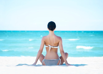Young, fit and beautiful girl meditating on a summer beach