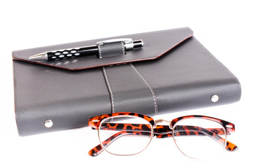 black luxury organizer and black pen with glasses isolated on wh